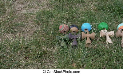 Collection of kendama toys sitting down on the grass