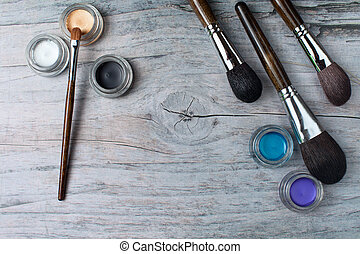 Collection of make up products on wooden background with copyspace