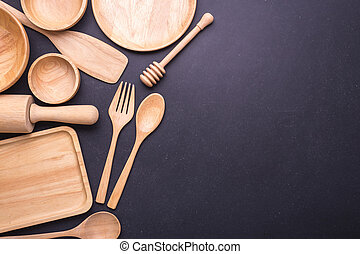 Collection of new wooden kitchen utensil, bowl, plate, spoon, dish. Studio shot on black table. With free space for text or design
