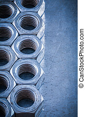 Collection of threaded nuts on scratched metallic background cop
