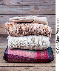 Collection of winter clothes knitwear on a wooden background