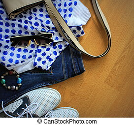 Collection of women's clothes. Jeans, shoes, bluose, glass. Top view