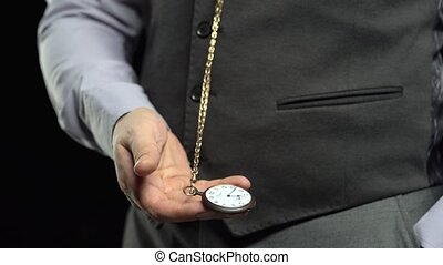 Collector pulls out a watch on a chain and puts time in his...