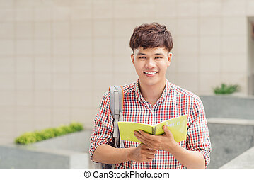 College asian male student holding book on the park