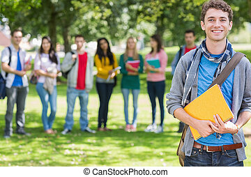 College boy holding books with students in park