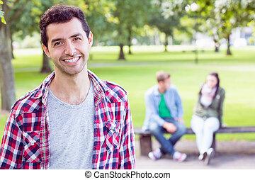 College boy smiling with blurred students sitting in park