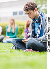College boy using table PC with blurred students in park