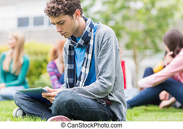 College boy using tablet PC with blurred students in park