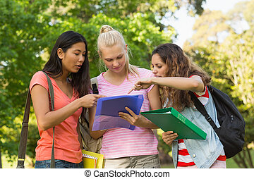 College friends looking at folder at campus
