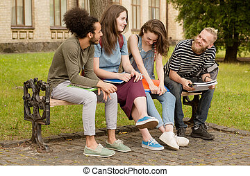 College friends sitting on bench in campus.