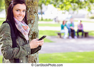 College girl text messaging with blurred students in park -...