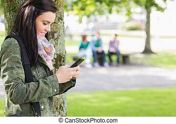 College girl text messaging with blurred students in park - ...