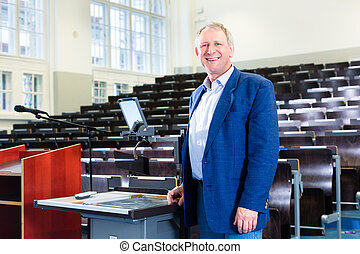 College professor in auditorium - College professor giving...