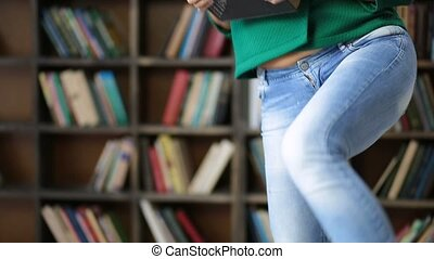 College student carrying pile of books in library