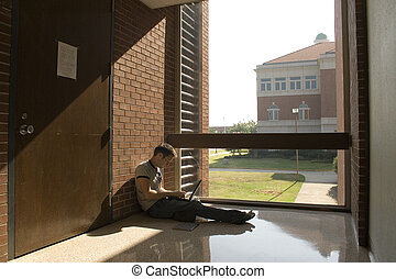 College Student - College student sitting in window working...