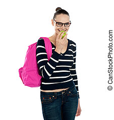 College student eating fresh green healthy apple