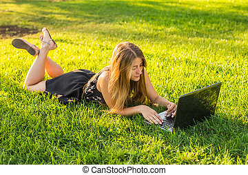 College student lying on the grass working on laptop at campus