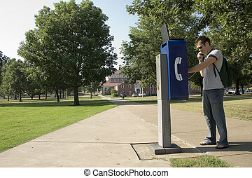 College Student - College student using campus payphone....