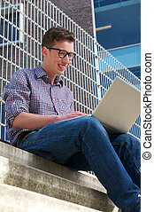 College student working on laptop outdoors