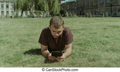 College student working on tablet on campus lawn -...