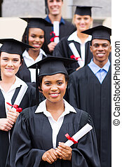 college students in graduation gown - group of college...