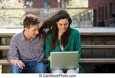 College students relaxing and looking at laptop outdoors