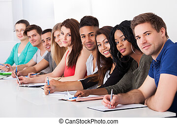 College Students Sitting In A Row At Desk - Portrait of...