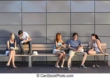 College students sitting on bench modern wall
