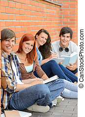 College students sitting outside by brick wall
