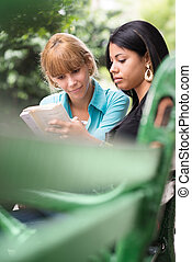 college students studying on textbook in park
