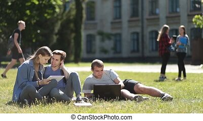 College students using laptop and tablet on lawn