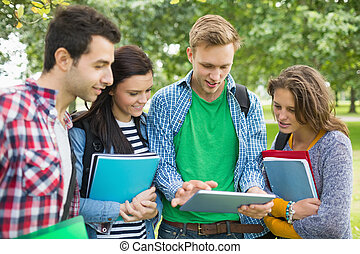 College students with bags and books using tablet PC in park