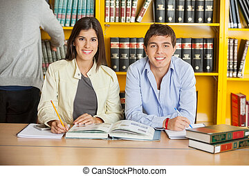 College Students With Books Sitting At Table In Library