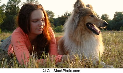 Collie dog with young girl on green field at sunlight