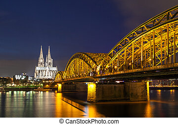 Cologne Cathedral with the Hohenzollern bridge at night -...