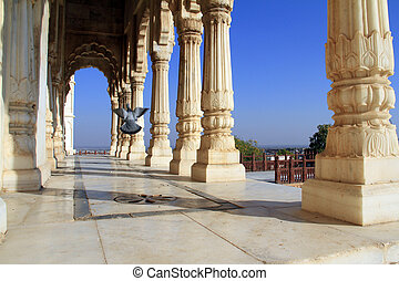 Colonade of white marble columns with flying pigeon