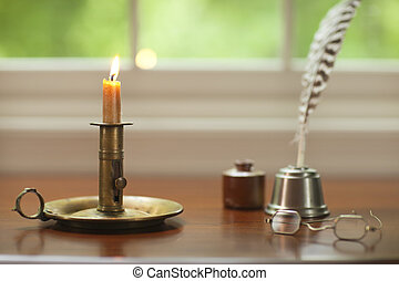 Colonial candle, quill pen and glasses on desk with window