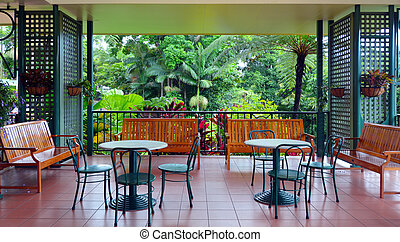 Colonial furnitures on a balcony against a tropical rain forest view