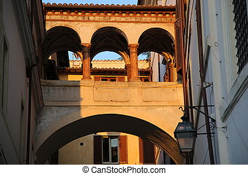 Colonnade connection between two medieval houses in the city of Spoleto at sunset