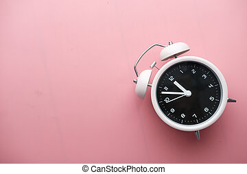color alarm clock on pink background, top view.