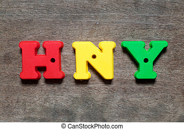 Color alphabet in word HNY (abbreviation of happy new year) on wood background