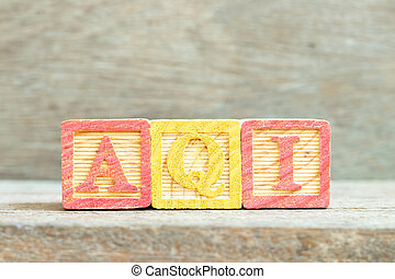 Color alphabet letter block in word AQI (Abbreviation of air quality index) on wood background