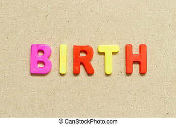 Color alphabet letter with word birth on wood background
