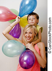 color balloons on white background, blond woman with little boy at birthday party bright smiling mother