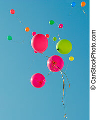Multi colored baloons flying up in the sky