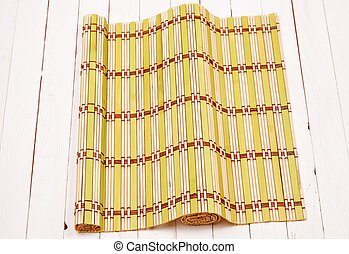 Color bamboo mat on a white wooden table