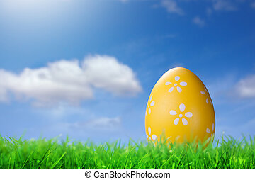 Color easter egg in the grass on blue