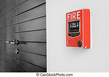color fire alarm switch on black and white wall
