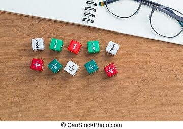 Color fraction dices, eyeglasses on blank white notebook on wooden desk
