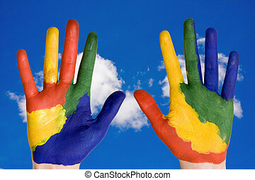 painted hands on blue sky background